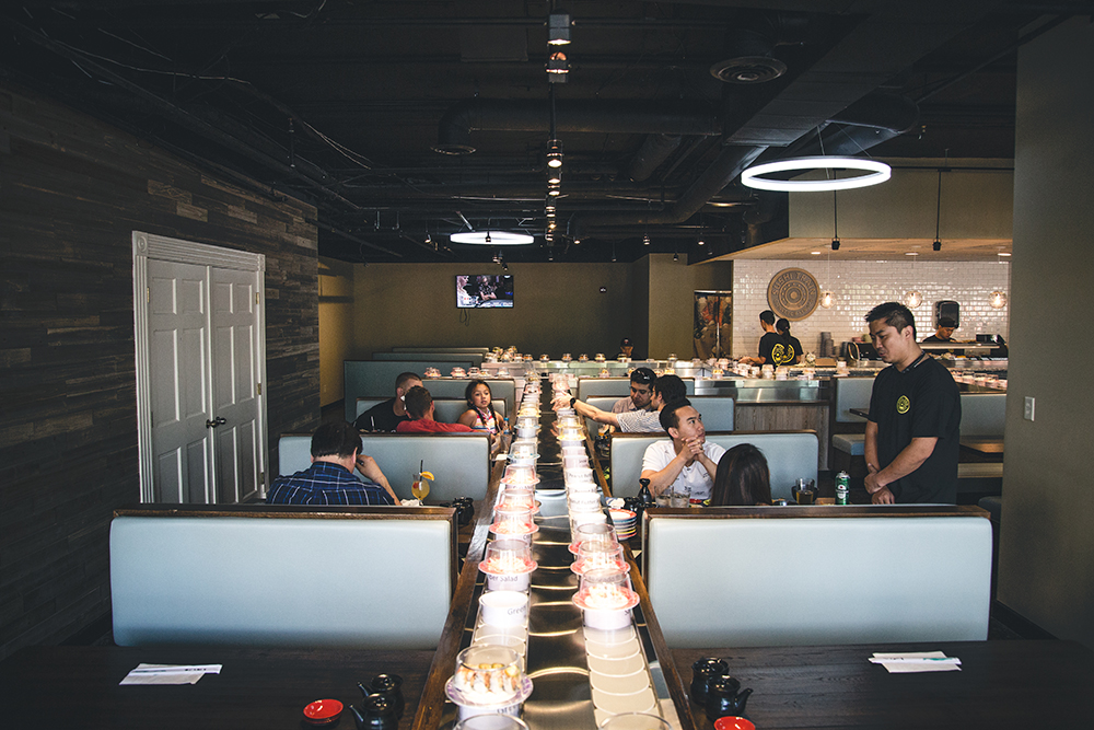 Sushi Train diners sit in booths as colored sushi plates scuttle alongside of them, available for anyone to grab as they pass by. The color of the plate determines the price // Photo by Sam Ziegler
