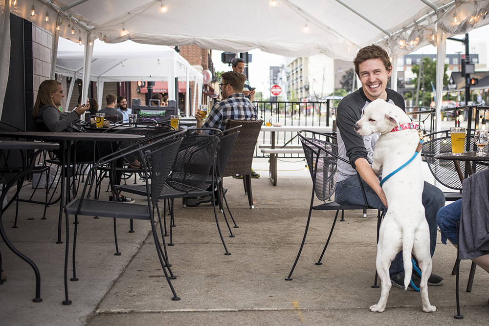 Blake Verdon with a dog in LTD Brewing Company's curbside seating area in Hopkins, Minnesota // Photo by Tj Turner