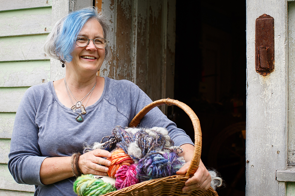 Andrea Myklebust with a basket of wool yarn // Photo by Barbara O'Brien Photography