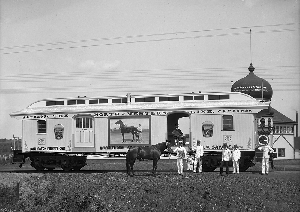 "A private car on the Dan Patch line stopped outside of the ""Taj Mahal"" in current day Savage, Minnesota. Dan Patch stands with workers in front of the car // Photo courtesy Minnesota Historical Society"