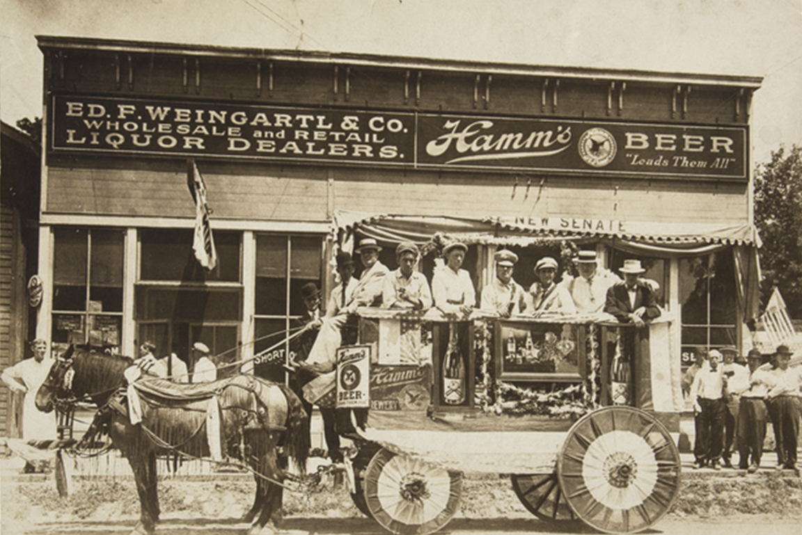 Horse-drawn wagon with streamers, riders and advertisements for Hamm's Beer, standing in front of Ed F. Weingartl and Company Liquor Dealers // Photo courtesy of Minnesota Historical Society