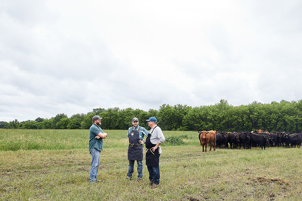 Andy Peterson of Peterson Craftsman Meats talks with Daniel Cataldo and Lenny Russo on his farm in Osceola, Wisconsin // Photo by Wing Ta
