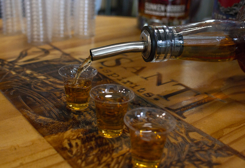 Schneider pours several tasters of his rye whiskey // Photo by Aaron Job