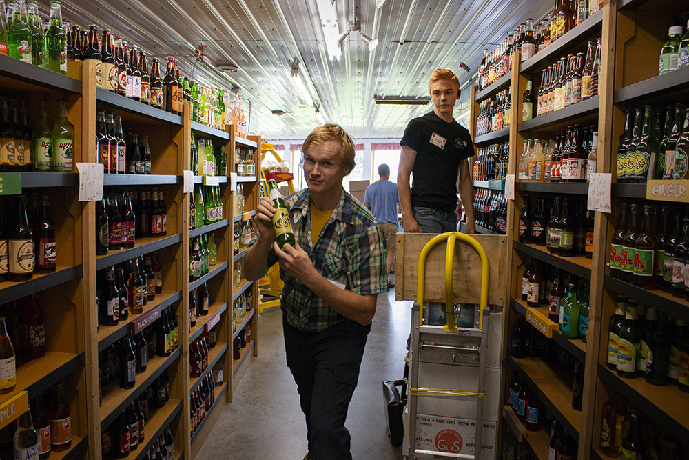 "Jerry ""The Soda Guy"" in one of the many aisles of soda. The dollies, like the one behind him, are all equipped with a gimmicky toy like a bicycle horn, or flashing strobe light. Energetic and enthusiastic is the best way to describe // Photo by Aaron Job"