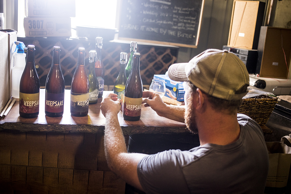 Watter's places labels on newly bottled ciders // Photo by Tj Turner