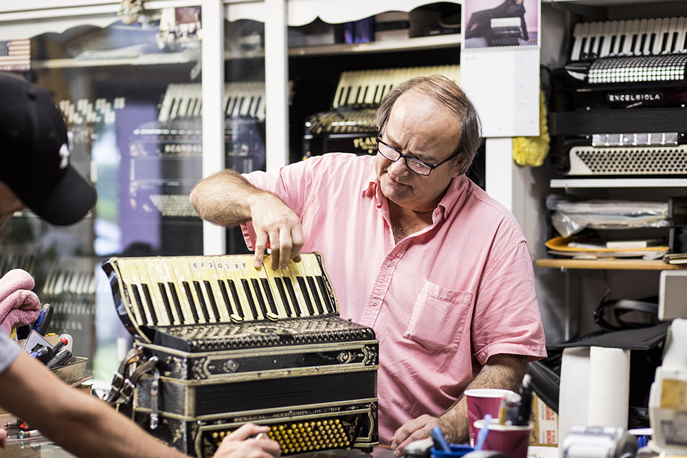 Ken Mahler examines an accordion // Photo by Tj Turner