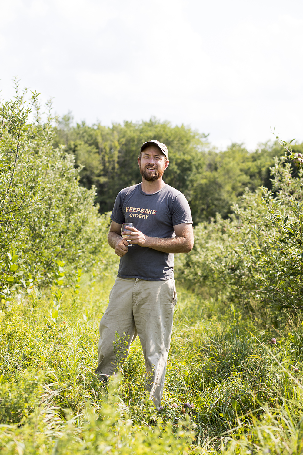 Nate Watters, co-owner and cidermaker at Keepsake Cidery, stands in between rows of apples on his Dundas, Minnesota orchard // Photo by Tj Turner