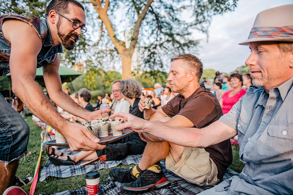 Scotty Reynolds, left, offers audience members a tray of food // Photo by Marie Ketring