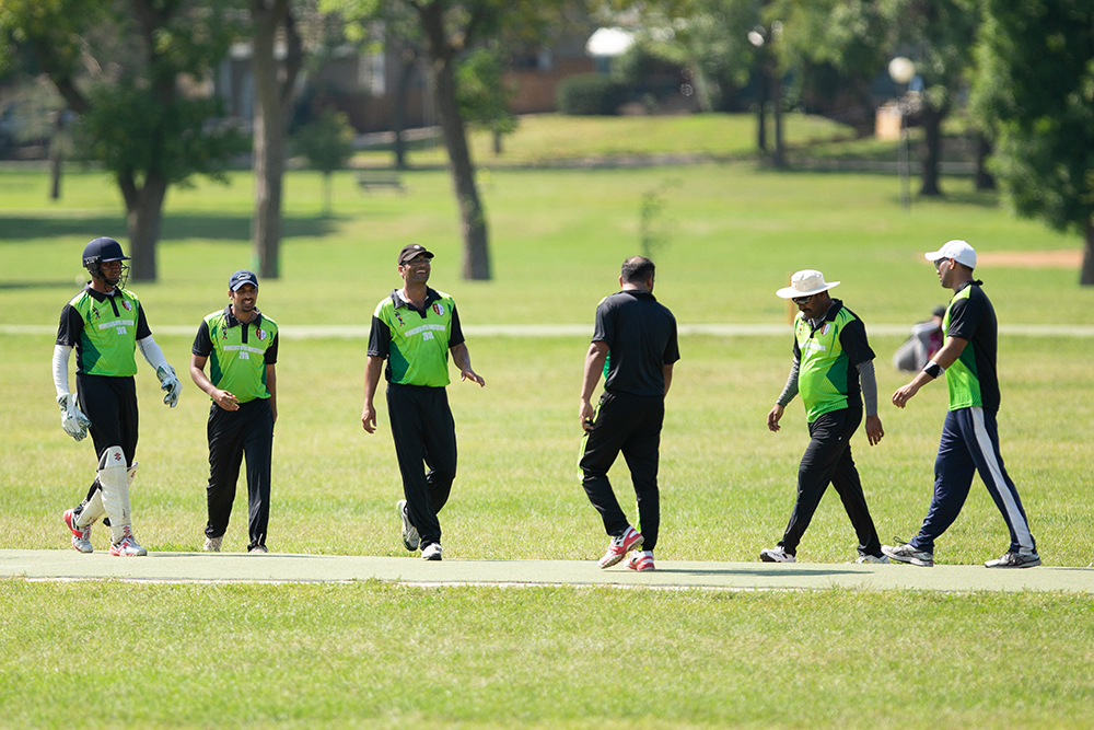 A group of cricketers convene during a match // Photo by Harrison Barden
