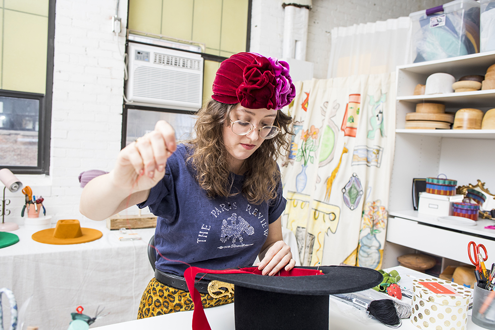 Milliner Celina Kane working on a hat in her shop // Photo by Tj Turner