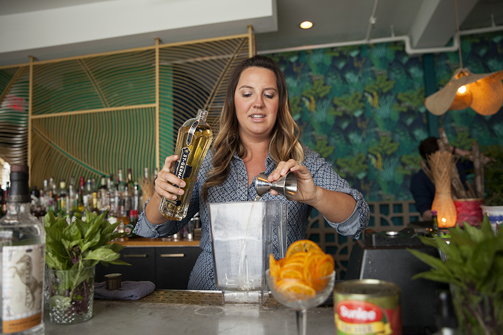 Bar Manager Christina Jenkins adding the St-Germain elderflower liqueur to the absinthe slushie mix // Photo by Katie Cannon