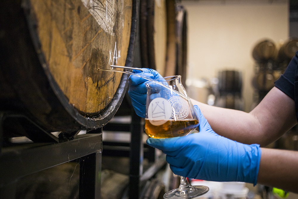 Indeed Brewing assistant brewery Tina Spurr pulling a nail from a Wooden Soul barrel // Photo by Tj Turner