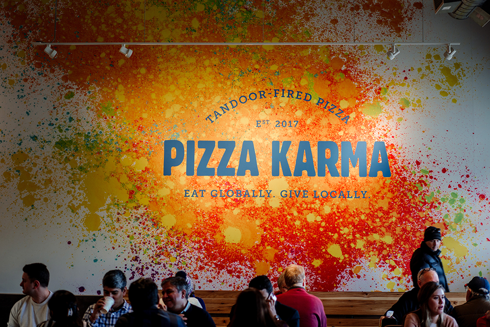 Diners eating their meals in front of the Pizza Karma sign within the restaurant // Photo by Becca Dilley