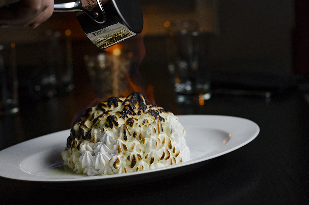Flaming Chartreuse liqueur is poured over the top of the Baked Alaska // Photo by Aaron Job