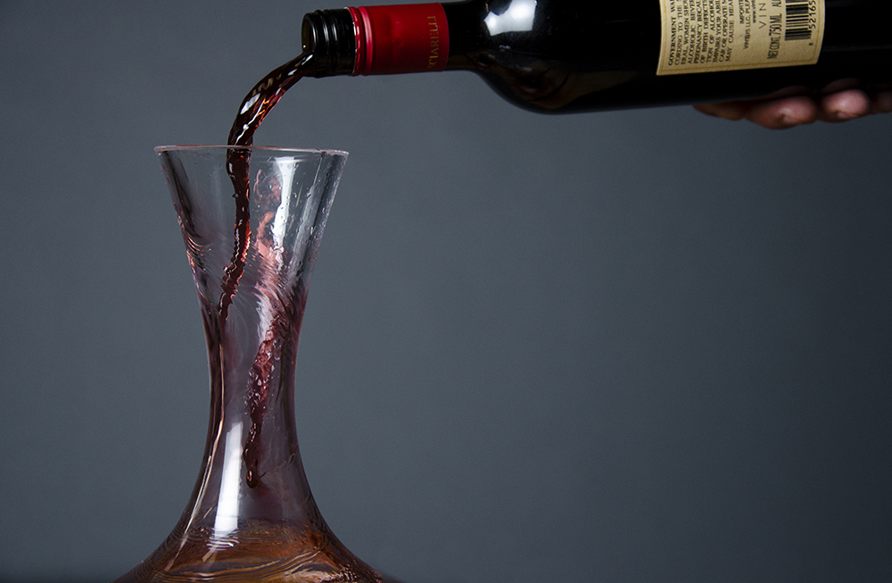 A bottle of wine being poured into a decanter // Photo by Aaron Job