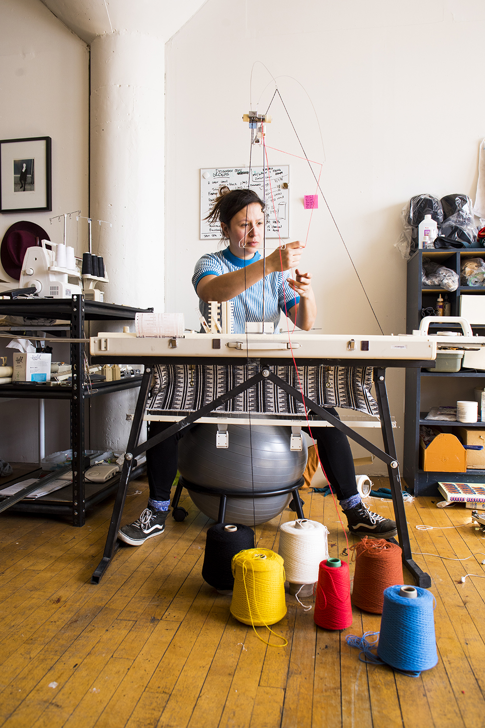 Thompson threading her knitting machine // Photo by Tj Turner