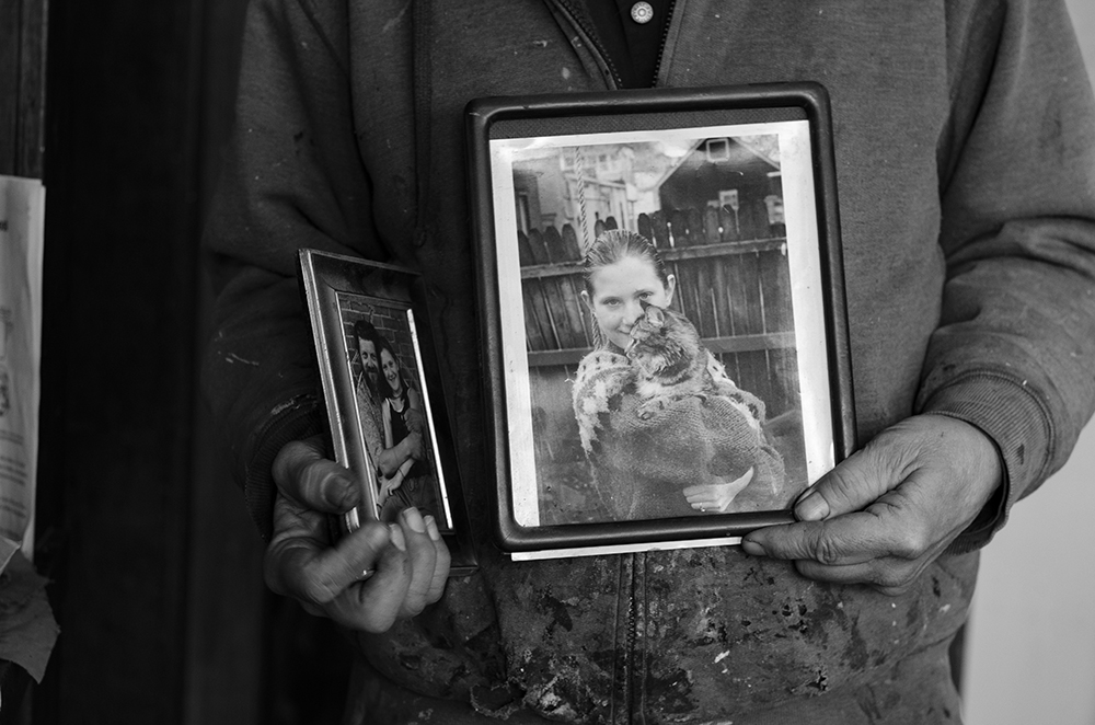 Phil holding up framed photos of his daughter Ayla that he took when she was younger // Photo by Aaron Job
