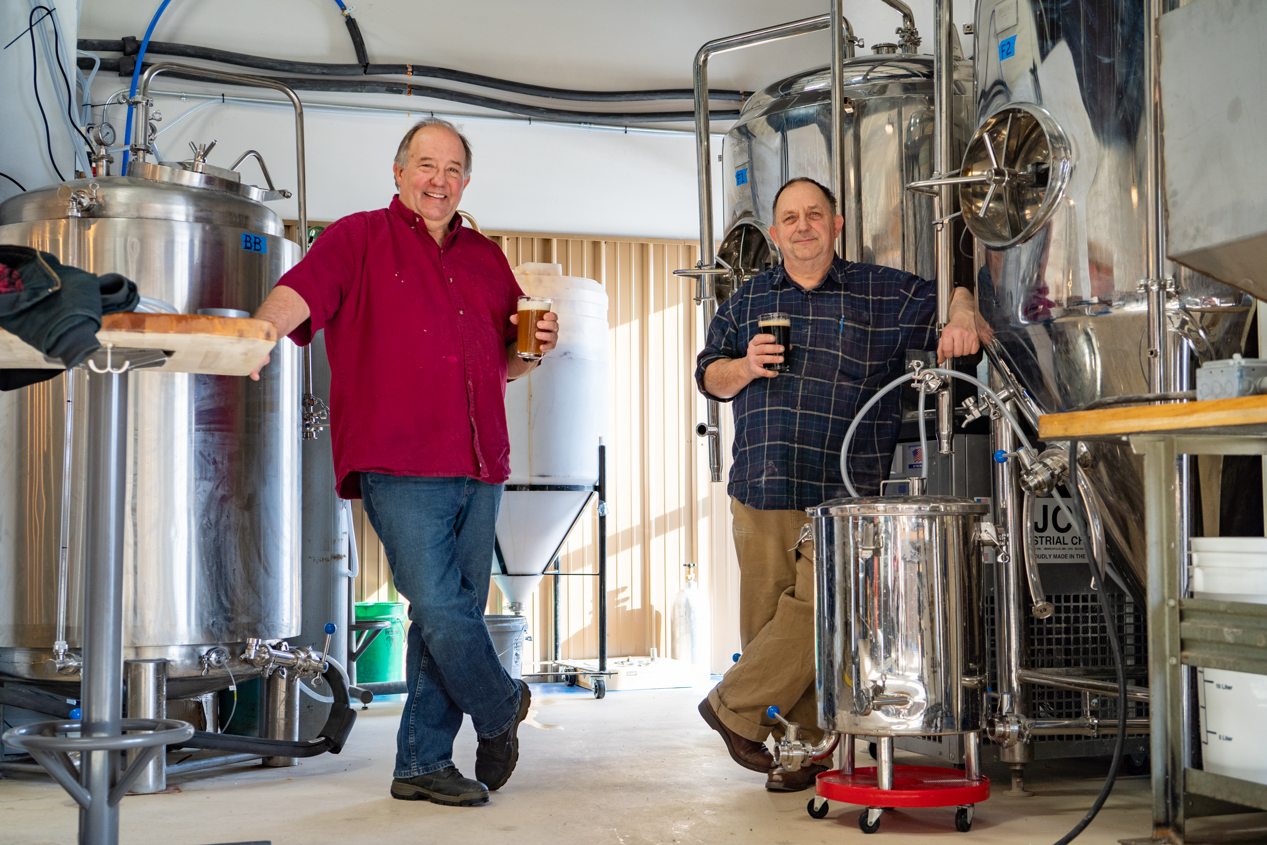 Brett Thunstrom, left, holds a lager and Warren Thunstrom holds a stout as they stand in the brewhouse of Thunder Brothers Brewing in Isanti // Photo by Tony Saunders