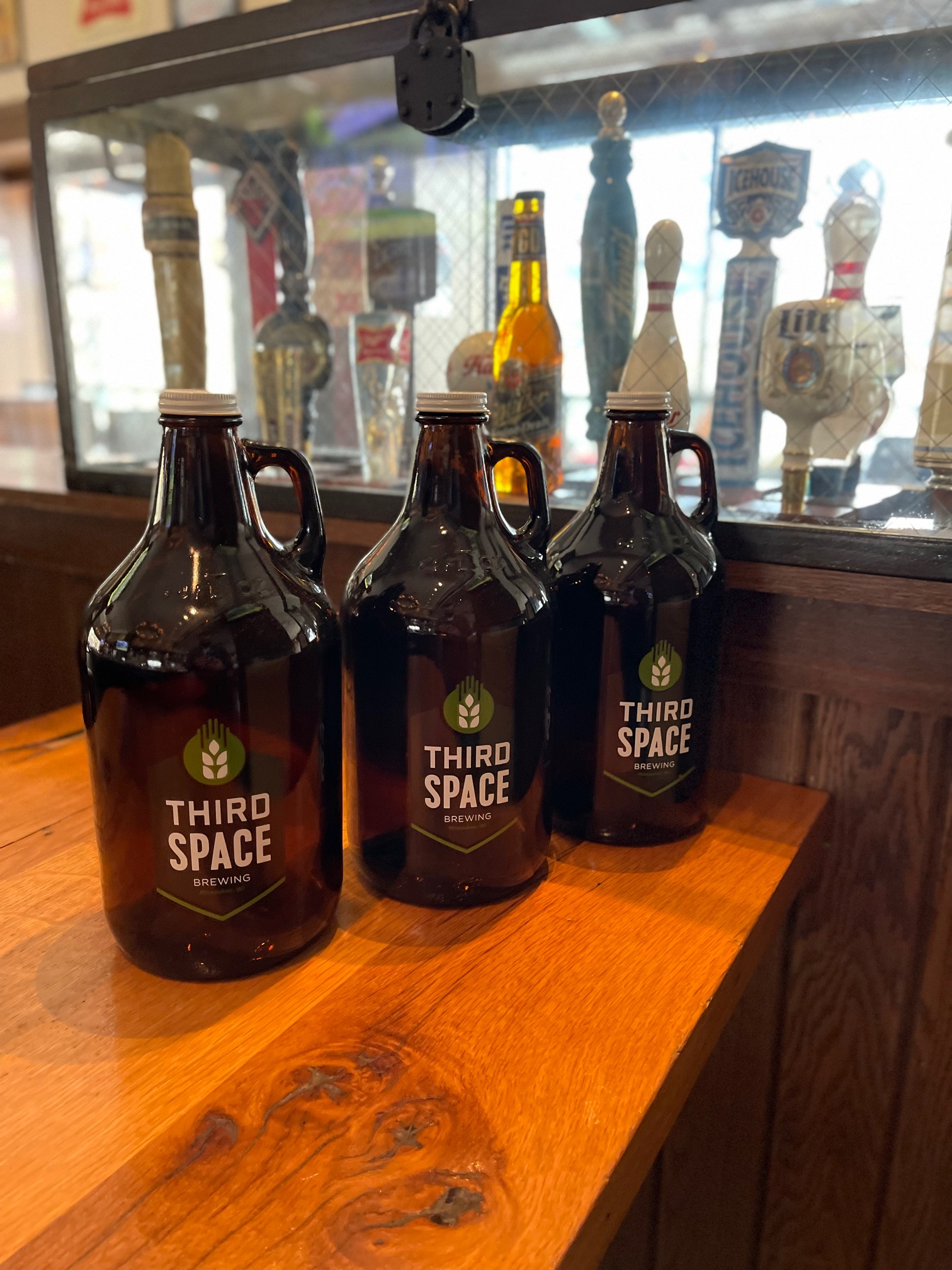 growlers of beer on bar table