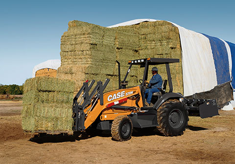 Tractor Loader moving hay bales