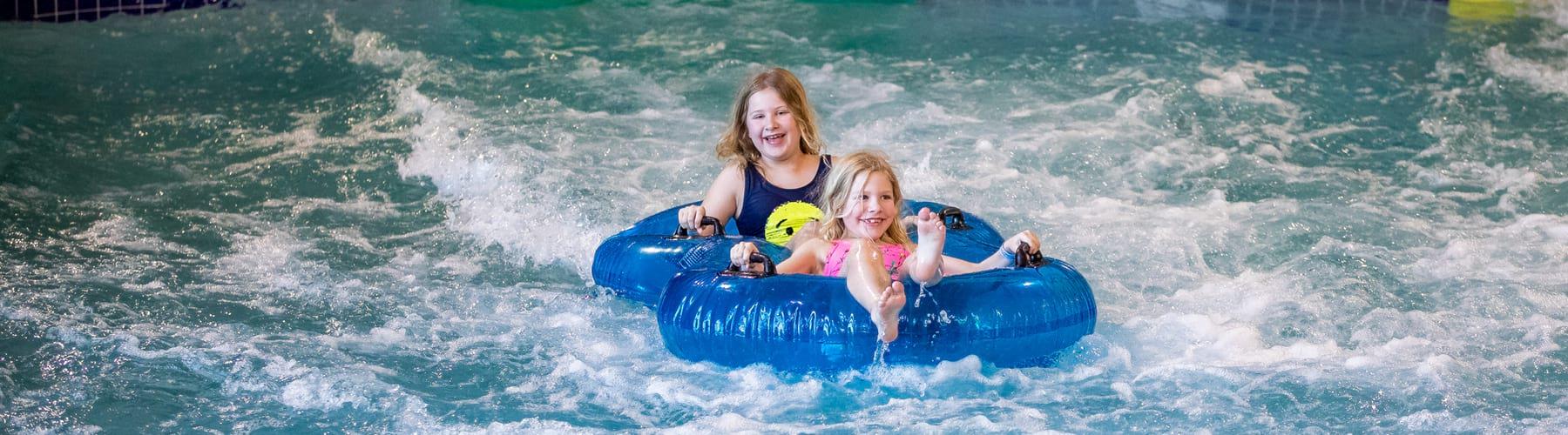 Girls on blue inner tube smiling