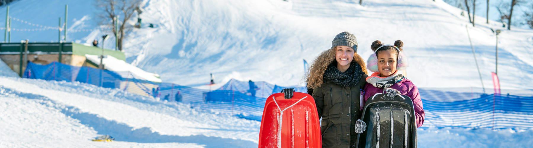 Two girls sledding