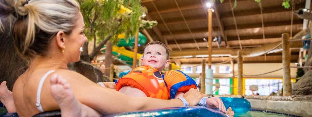 Happy mom and endearing son in a swim ring at indoor waterpark | Timber Ridge Lodge
