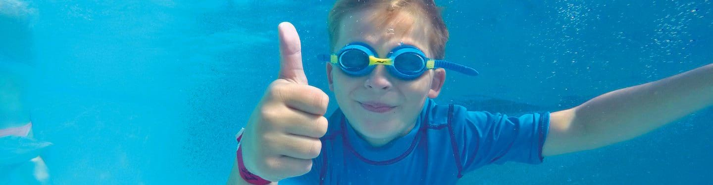 Boy swimming underwater giving a thumbs up