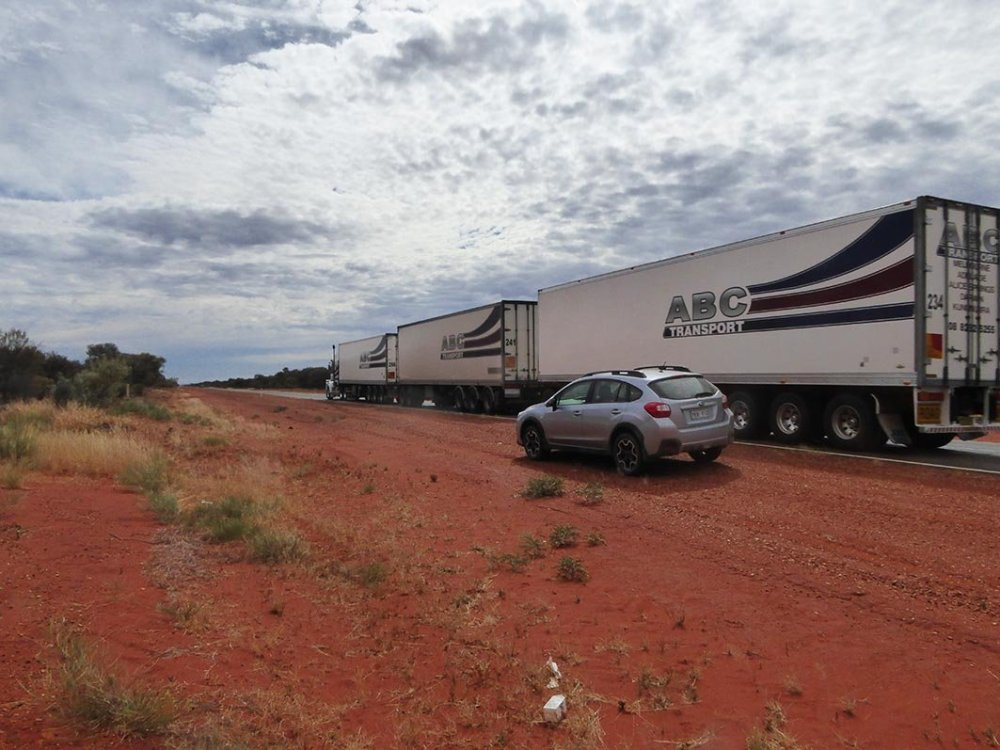 Car with road train passing.jpg