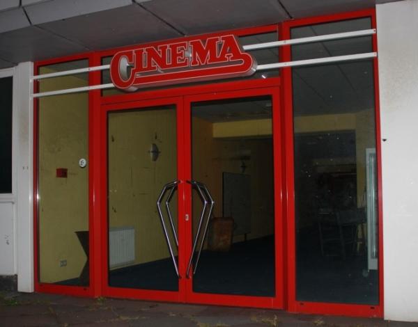 Foto mit einer Aufnahme von der ehemaligen Eingangstür; über der Tür ist die alte Leuchtreklame mit dem Logo des CINEMA zu sehen.