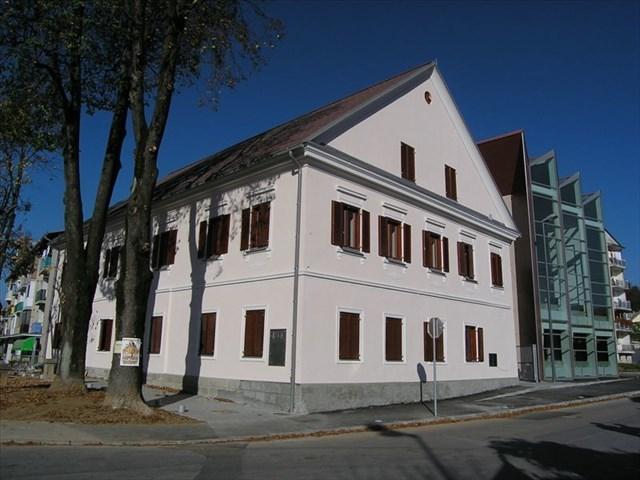 Obnovljena Koščakova hiša s prizidkom v ozadju.