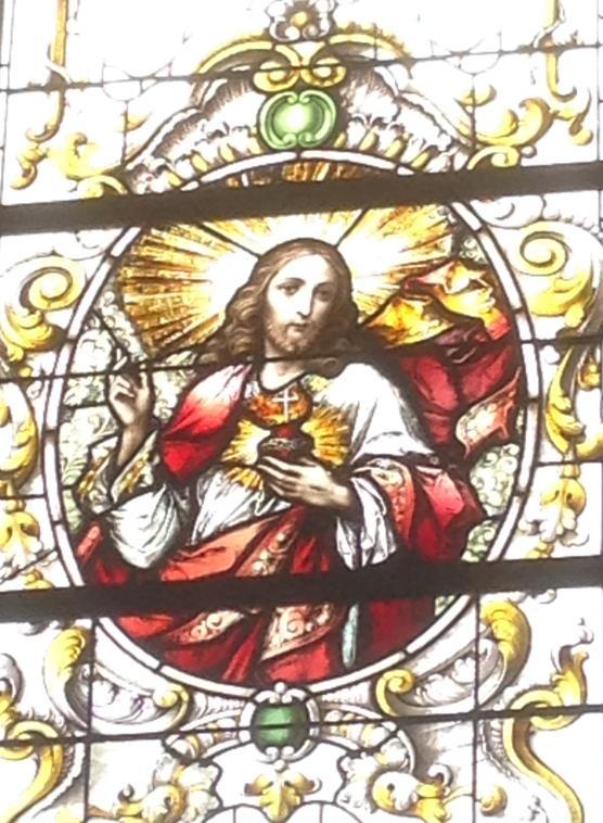 Fensterbild 2: Mann mit rot/weißem Gewand hält etwas Rotes mit Kreuz