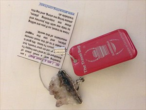Red travel bug tag with a piece of amythest stone