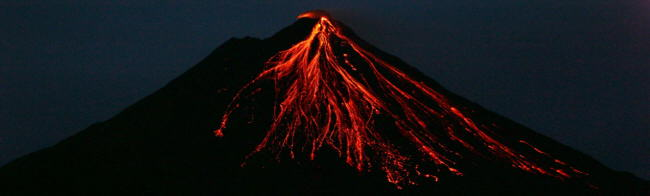 Lava flowing down the slope of Arenal Volcano on a clear night