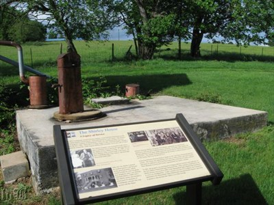 The CWDT marker is right behind the house along a walkway and faces an old water pump.