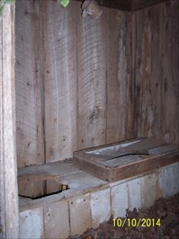 Inside photo of Outhouse at Whitesand Church, by MountainWoods.  Not sure what that framework was on the second seat.