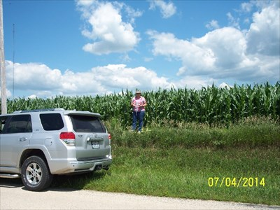 Lee County High Point, by MountainWoods. My wife is holding the GPSr at the highest point in Lee County, Illinois.  As you can see, since she is about 5 foot 5 inches, the corn is DEFINITELY more than knee high by the 4th of July.  This is typical of the fertile lands of Illinois; but even more so on a rather wet year.