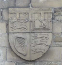 The coat of arms is the same as the monarch's except that the 3 bars at the top show he is still the Heir Apparent and not yet crowned as the monarch.