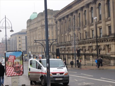 As you start to walk along Bridge Street you will see the 'J C Decaux' advertising sign. On the right hand side can be seen St. Georges Hall.