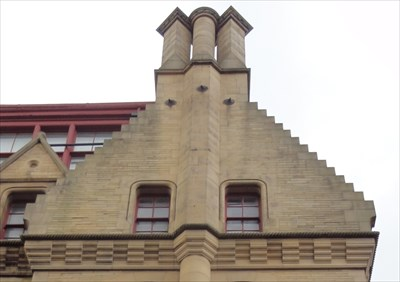 The triple stack stands at the top of a stepped pyramid pediment. The stone detail under the windows follows through round the outside of the flue.