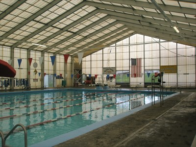 The pool is housed within a structure made of translucent corrugated fiberglass.  It lets in a lot of natural light, and it keeps off the rain which is very important in the Pacific Northwest.
