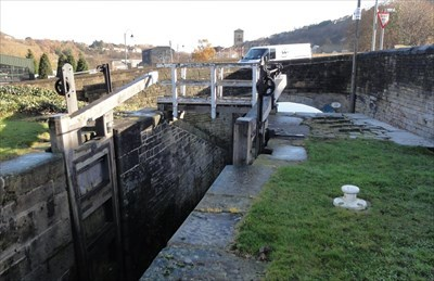 The gates have been left open. The wooden footbridge can be seen on top of the lock with the stone road bridge just behind it.