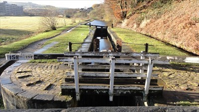 The wooden footbridge can be seen that gives access to both sides of the canal. The double set of lock numbers can also be seen.