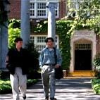 Image is of two young men walking past or through the waypoint.  Pillars are visible.