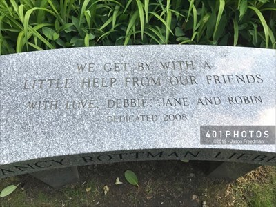 The top face of the seat is engraved: <br> WE GET BY WITH A <br> LITTLE HELP FROM OUR FRIENDS <br> WITH LOVE, DEBBIE, JANE, AND ROBIN <br> DEDICATED 2008