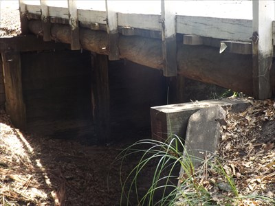A side view from the west, showing one of the wooden post bearers and wooden plank abutments. Dry creek today.