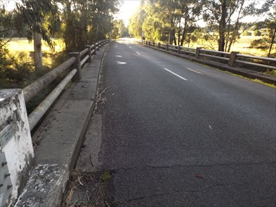 The plaque is on the left edge of the photo, showing the narrow ledge for pedestrian traffic, and PSM 1575-2 is at the far end of the bridge.