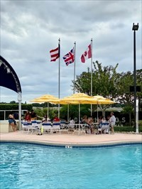 Six flags flank a fabric covered bandstand to the west of a Waters Edge swimming pool at Orange Lake Resort in Kissimmee, Florida. The flags of Puerto Rico, United Kingdom and Canada fly north of the stage.