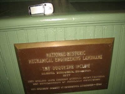 The plaque is mounted about waist high in the lobby area of the top building.