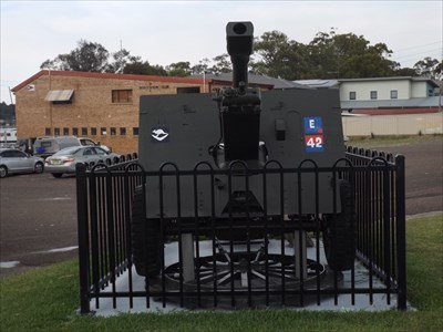 Front-on view of this fenced piece of artillery, out the front of the Wangi Returned Services League Club.
